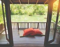 Ξύλινο patio σε μια πράσινη λίμνη χαλάρωσης με το χαλί και τα μαξιλάρια μπαμπού Στοκ Φωτογραφίες
