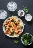 Οβελίδια σολομών, ελιές, σπανάκι, νερό πάγου - πίνακας πρόχειρων φαγητών Ψημένο στη σχάρα οβελίδιο ψαριών σολομών σε ένα σκοτεινό Στοκ εικόνες με δικαίωμα ελεύθερης χρήσης