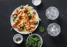 Οβελίδια σολομών, ελιές, σπανάκι, νερό πάγου - πίνακας πρόχειρων φαγητών Ψημένο στη σχάρα οβελίδιο ψαριών σολομών σε ένα σκοτεινό Στοκ Εικόνα
