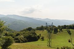 Ογκώδης πόλος ηλεκτρικής ενέργειας στη φύση, πράσινα καλυμμένα βλάστηση βουνά στο υπόβαθρο στυλοβάτης ηλεκτρικής ενέργειας υψηλής Στοκ εικόνες με δικαίωμα ελεύθερης χρήσης
