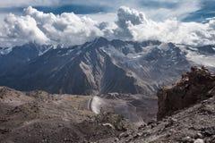 Ογκώδης κορυφογραμμή βουνών, ηλιόλουστη ημέρα, μπλε ουρανός με τα άσπρα σύννεφα Στοκ Εικόνα