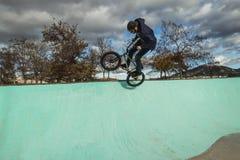 Οδήγηση αγοριών και ποδήλατο άλματος bmx σε ένα πάρκο ακραίος αθλητισμός στοκ φωτογραφία