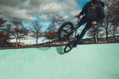 Οδήγηση αγοριών και ποδήλατο άλματος bmx σε ένα πάρκο ακραίος αθλητισμός στοκ εικόνες