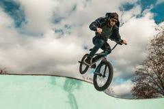 Οδήγηση αγοριών και ποδήλατο άλματος bmx σε ένα πάρκο ακραίος αθλητισμός στοκ φωτογραφίες