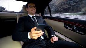 Οδήγηση επιχειρηματιών χαμόγελου όμορφη στο αυτοκίνητο πολυτέλειας, που διαβάζει τις καλές ειδήσεις στο τηλέφωνο στοκ εικόνα με δικαίωμα ελεύθερης χρήσης