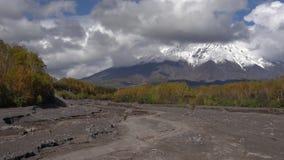 Οδήγηση μοτοσικλετών στο δρόμο υποστηριγμάτων στον ξηρό ποταμό στην κατεύθυνση του ηφαιστείου φιλμ μικρού μήκους