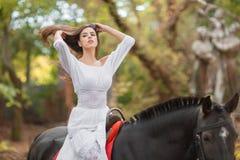 Οδήγηση πλατών αλόγου Όμορφη νέα γυναίκα σε ένα άσπρο φόρεμα που οδηγά σε ένα καφετί άλογο υπαίθρια Στοκ εικόνα με δικαίωμα ελεύθερης χρήσης