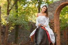 Οδήγηση πλατών αλόγου Όμορφη νέα γυναίκα σε ένα άσπρο φόρεμα που οδηγά σε ένα καφετί άλογο υπαίθρια Στοκ Εικόνα
