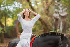 Οδήγηση πλατών αλόγου Όμορφη νέα γυναίκα σε ένα άσπρο φόρεμα που οδηγά σε ένα καφετί άλογο υπαίθρια Στοκ Εικόνες