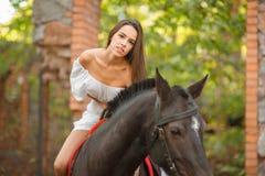 Οδήγηση πλατών αλόγου Όμορφη νέα γυναίκα σε ένα άσπρο φόρεμα που οδηγά σε ένα καφετί άλογο υπαίθρια Στοκ Φωτογραφίες