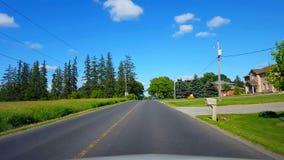 Οδήγηση του αγροτικού δρόμου κατά μήκος των κατοικημένων σπιτιών κατά τη διάρκεια της φωτεινής θερινής ημέρας POV άποψης οδηγών ό