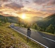 Οδήγηση Motorbiker στις αυστριακές Άλπεις στο όμορφο ηλιοβασίλεμα δραματικό Στοκ Φωτογραφίες