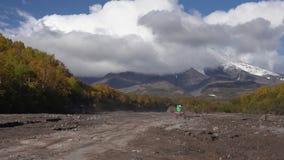 Οδήγηση Quadracycle στο δρόμο υποστηριγμάτων στον ξηρό ποταμό στην κατεύθυνση του ηφαιστείου απόθεμα βίντεο