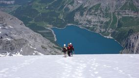 Οδηγός βουνών με δύο πελάτες που κατεβαίνουν έναν απότομο άσπρο παγετώνα με μια φανταστική μπλε λίμνη βουνών μακριά κατωτέρω Στοκ εικόνα με δικαίωμα ελεύθερης χρήσης