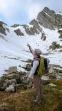 Οδηγός βουνών που δείχνει στην κορυφή και που αναρριχείται στη διαδρομή ως εξήγηση για έναν πελάτη Στοκ εικόνα με δικαίωμα ελεύθερης χρήσης