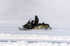 Οδηγώντας αθλητικό όχημα για το χιόνι ατόμων στο φινλανδικό Lapland σε μια ηλιόλουστη ημέρα Στοκ εικόνα με δικαίωμα ελεύθερης χρήσης