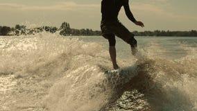 Οδηγώντας κύμα Surfer στο wakeboard σε σε αργή κίνηση Άτομο που κάνει σερφ στο ηλιοβασίλεμα απόθεμα βίντεο