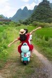 Οδηγώντας μοτοσικλέτα ζεύγους γύρω από τους τομείς ρυζιού Yangshuo, Κίνα στοκ εικόνες