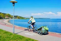 Οδηγώντας οβελός Curonian θερέτρου της Nida ποδηλάτων ατόμων και η θάλασσα της Βαλτικής στοκ φωτογραφία