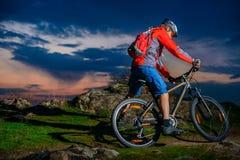 Οδηγώντας ποδήλατο βουνών ποδηλατών στο δύσκολο ίχνος ανοίξεων στο όμορφο ηλιοβασίλεμα Ακραίος αθλητισμός και έννοια περιπέτειας στοκ φωτογραφίες με δικαίωμα ελεύθερης χρήσης
