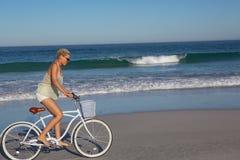 Οδηγώντας ποδήλατο γυναικών στην παραλία στην ηλιοφάνεια στοκ εικόνα με δικαίωμα ελεύθερης χρήσης