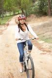 Οδηγώντας ποδήλατο γυναικών στο πάρκο στοκ φωτογραφίες