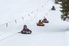 Οδηγώντας σωλήνας χιονιού κοριτσιών στοκ φωτογραφίες