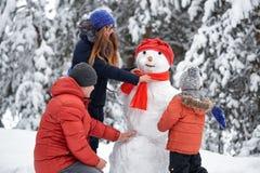 οδηγώντας χειμώνας ελκήθρων διασκέδασης ένα κορίτσι, ένα άτομο και ένα αγόρι που κάνουν έναν χιονάνθρωπο Στοκ Εικόνες