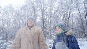 οδηγώντας χειμώνας ελκήθρων διασκέδασης Ευτυχείς μητέρα και γιος που ρίχνουν το χιόνι στον αέρα στο χειμερινό δάσος ή το πάρκο απόθεμα βίντεο