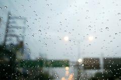 Οδική άποψη μέσω του παραθύρου αυτοκινήτων με τις σταγόνες βροχής Στοκ Εικόνα