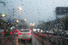 Οδική άποψη μέσω του παραθύρου αυτοκινήτων με τις σταγόνες βροχής Στοκ Εικόνες