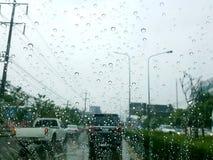 Οδική άποψη μέσω του παραθύρου αυτοκινήτων με τις σταγόνες βροχής Στοκ Φωτογραφία