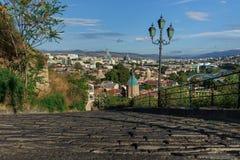 Οδική επίστρωση στο υπόβαθρο του πανοράματος της πόλης του Tbilisi στοκ φωτογραφία