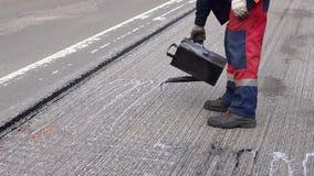 Οδική επισκευή Οι λεπτομέρειες εργασίας, εργαζόμενοι χύνουν την οδική επιφάνεια ρητίνης για να καλύψουν την άσφαλτο απόθεμα βίντεο