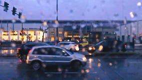 Οδική κυκλοφορία κατά τη διάρκεια μιας βροχερής ημέρας με τις πτώσεις νερού στο πρώτο πλάνο που ρέουν απόθεμα βίντεο