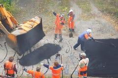 Οδική οδός που επισκευάζει τις εργασίες Εργάτες οικοδομών κατά τη διάρκεια του ασφαλτώνοντας δρόμου στοκ φωτογραφία με δικαίωμα ελεύθερης χρήσης