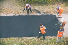 Οδική οδός που επισκευάζει τις εργασίες Εργάτες οικοδομών κατά τη διάρκεια του ασφαλτώνοντας δρόμου στοκ φωτογραφία
