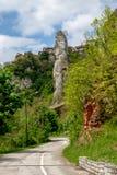 Οδική στροφή βουνών κάτω από τον επικό ουρανό με τα σύννεφα και το πέος που μοιάζει με τον πέτρινο απότομο βράχο στοκ εικόνες