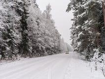 Οδική στροφή και ερχόμενο αυτοκίνητο στο χειμερινό δάσος Στοκ εικόνα με δικαίωμα ελεύθερης χρήσης