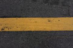 Οδική σύσταση κινηματογραφήσεων σε πρώτο πλάνο και κίτρινο λωρίδα στοκ εικόνα