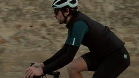 Οδικοί ποδηλάτες που οδηγούν στο δρόμο βουνών ηλιοβασιλέματος απόθεμα βίντεο