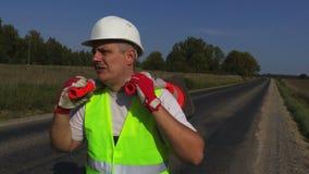Οδικός εργαζόμενος με δύο κώνους κυκλοφορίας που περιμένει στην εθνική οδό απόθεμα βίντεο