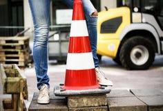 Οδικός πλαστικός κώνος και λεπτά θηλυκά πόδια, οδικό έργο Στοκ Εικόνες