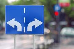 Οδικό σημάδι με τα αντίθετα βέλη στο υπόβαθρο ράβδων δύο και οδών Στοκ εικόνες με δικαίωμα ελεύθερης χρήσης