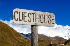 Οδικό σημάδι πληροφοριών, δείκτης με την επιγραφή - guesthouse - στα βουνά Στοκ Φωτογραφίες