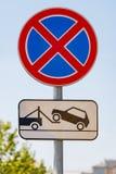 Οδικό σημάδι που απαγορεύει την παύση του αυτοκινήτου με μια πινακίδα φορτηγών ρυμούλκησης ενάντια στο μπλε ουρανό στην ηλιόλουστ στοκ εικόνες
