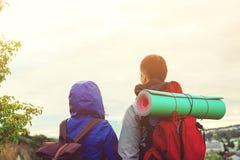 Οδοιπόροι με τα σακίδια πλάτης πάνω από το βουνό που απολαμβάνουν τη ζωή και την όμορφη θέα σχετικά με την κοιλάδα στοκ φωτογραφίες