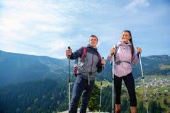 Οδοιπόροι με τα σακίδια πλάτης που χαλαρώνουν πάνω από ένα βουνό και που απολαμβάνουν τη θέα της κοιλάδας στοκ εικόνες