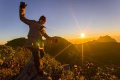 Οδοιπόροι που χαλαρώνουν πάνω από ένα βουνό και που απολαμβάνουν τη θέα του va Στοκ Φωτογραφία