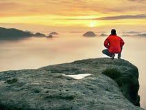 Οδοιπόρος ατόμων στην αιχμή βουνών Θαυμάσια χαραυγή στο misty τοπίο φθινοπώρου Ήλιος που κρύβεται στα σύννεφα Στοκ Εικόνες